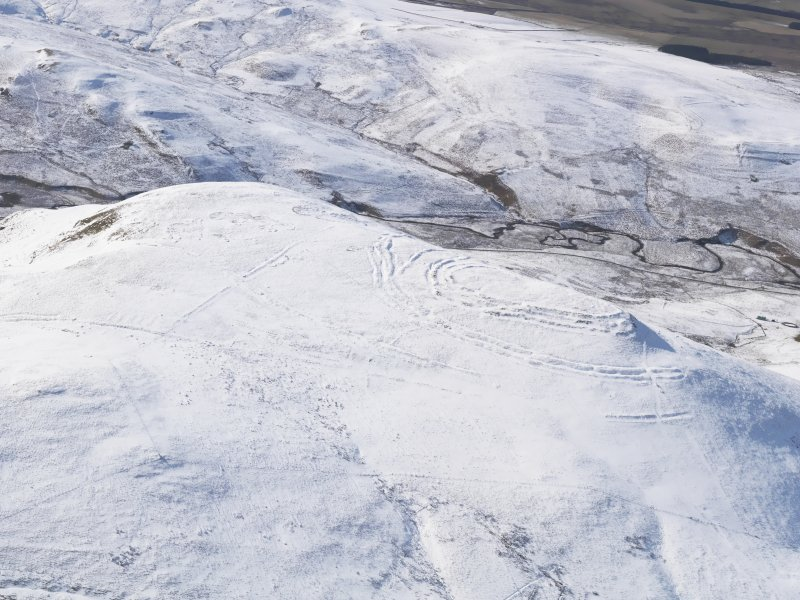 General oblique aerial view of Woden Law fort and linear earthworks in snow, looking WSW.