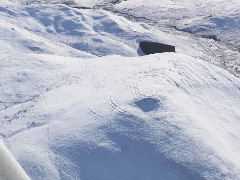 General oblique aerial view of Woden Law fort and linear earthworks in snow, looking, looking SSW.