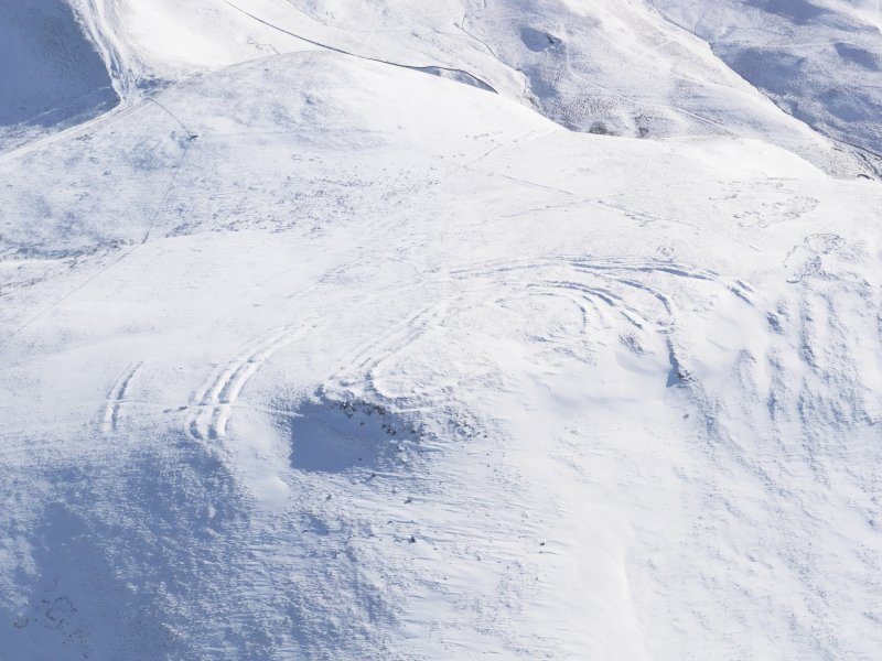 General oblique aerial view of Woden Law fort and linear earthworks in snow, looking S.