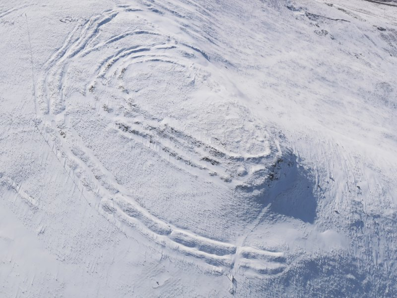 Oblique aerial view of Woden Law fort and linear earthworks in snow, looking SW.
