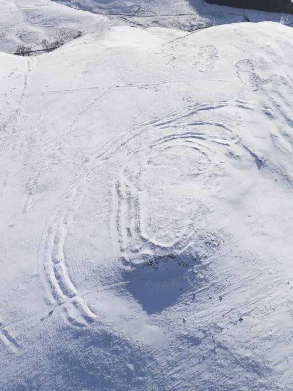 Oblique aerial view of Woden Law fort and linear earthworks in snow, looking S.