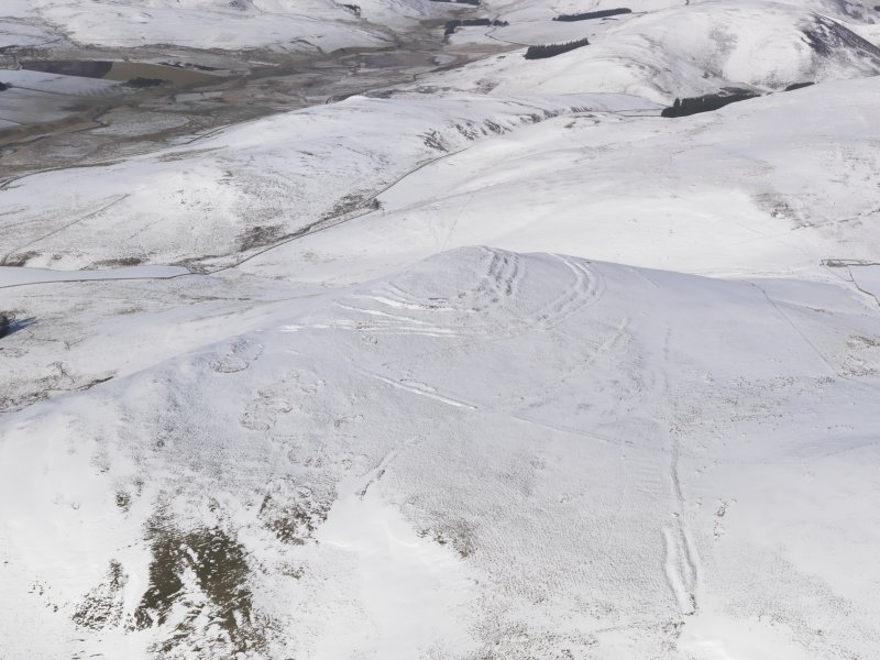 General oblique aerial view of Woden Law fort and linear earthworks in snow, looking N.