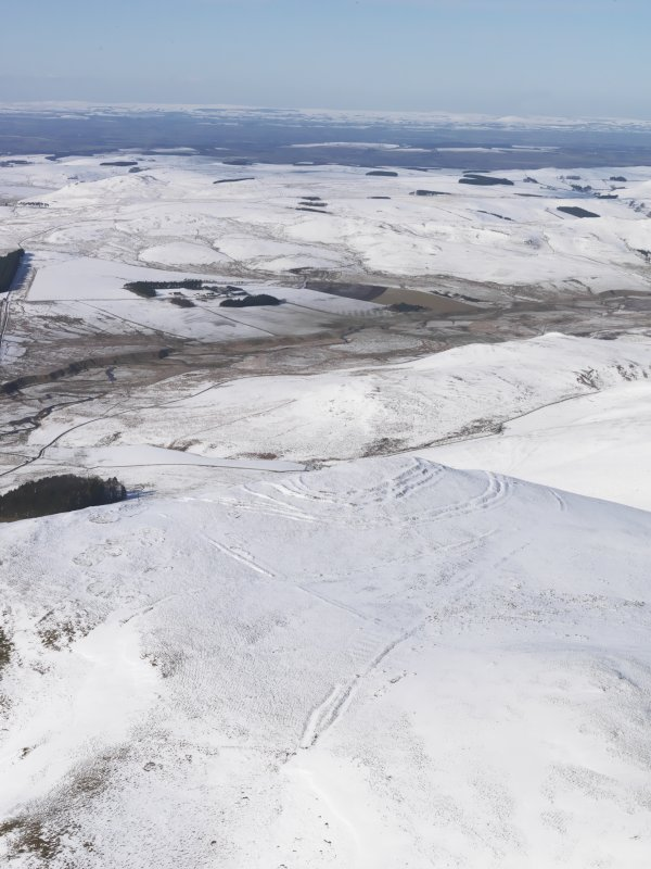 General oblique aerial view of Woden Law fort and linear earthworks in snow, looking NW