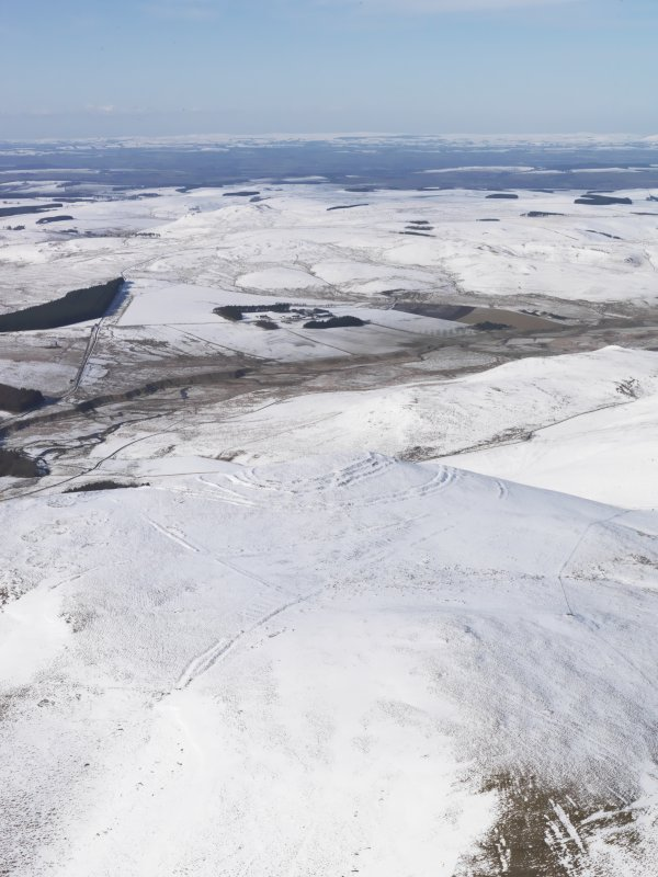 General oblique aerial view of Woden Law fort and linear earthworks in snow, looking NW.