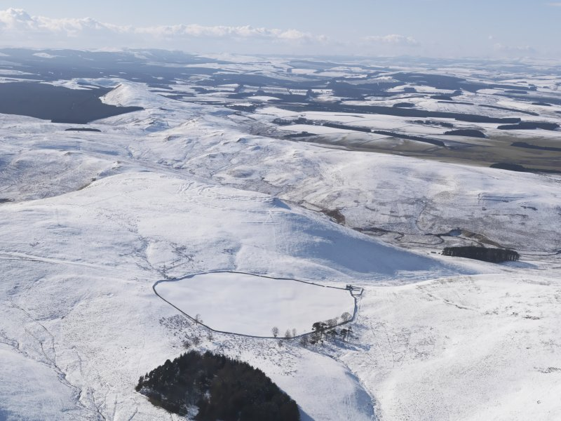 General  view of Woden Law fort and linear earthworks, and the Roman road in snow, looking WSW.