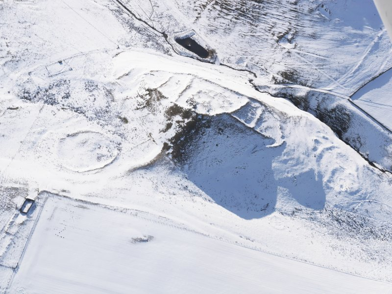 Oblique aerial view of fort, scooped settlement, enclosure and settlement, buildings, enclosures and sheepfolds under snow, looking to SW.