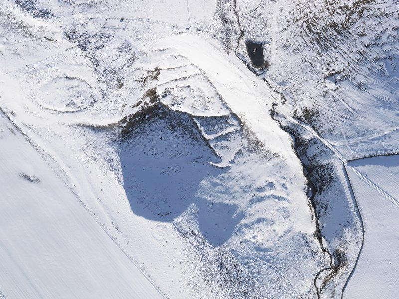 Oblique aerial view of fort, scooped settlement, enclosure and settlement, buildings, enclosures and sheepfolds under snow, looking to S.