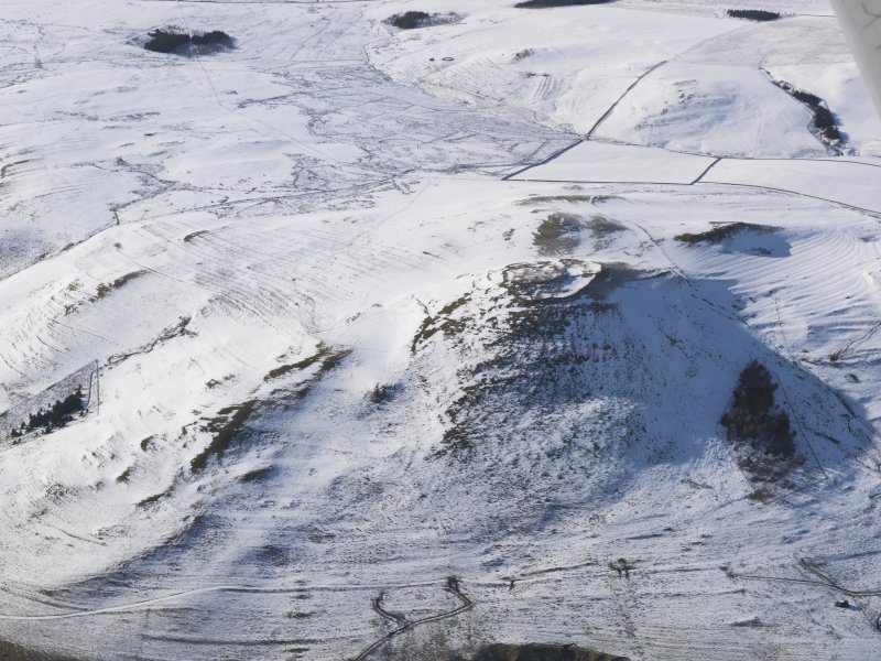 General aerial view of fort, scooped settlement, enclosure, rig and furrow, cultivation terraces and field systems under snow, looking to W.