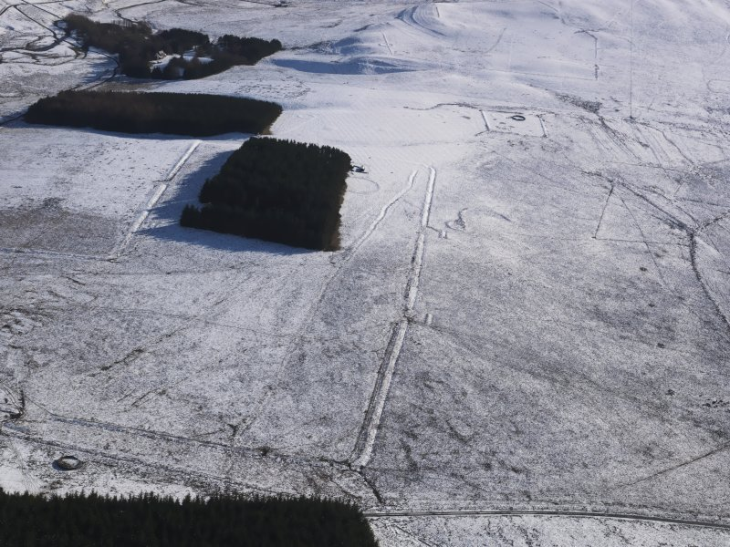 General aerial view of Roman temporary camps and linear earthwork under snow, looking to SSE.