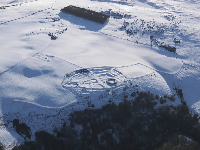 Oblique aerial view of Edin's Hall broch and fort under snow.