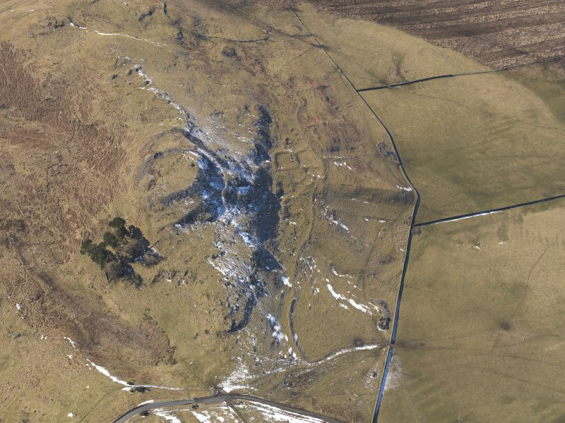 Oblique aerial view of Dreva Craig fort, settlements and field system, looking WSW.