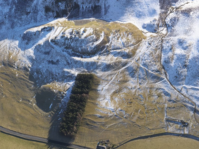 Oblique aerial view of Tinnis Castle and fort, building, platform, settlement and track, burnt mound, enclosure and cultivation terraces under snow, looking SSW.