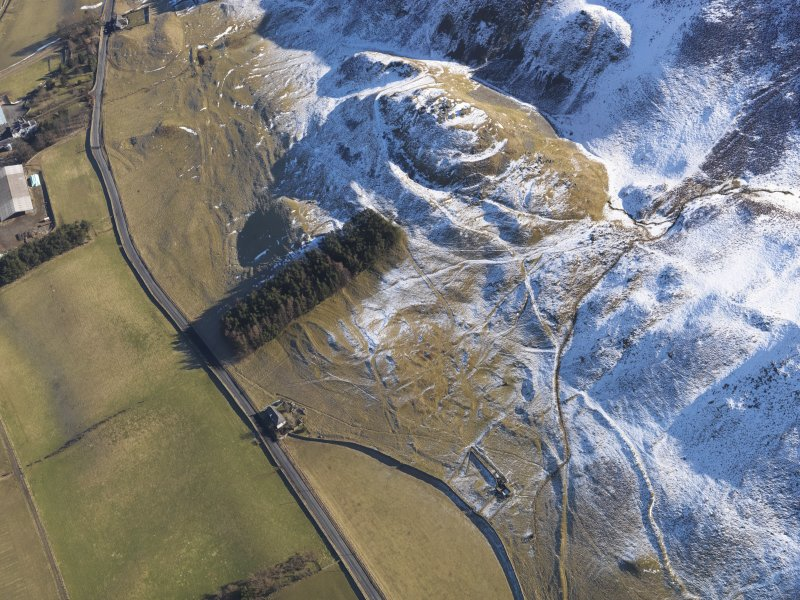Oblique aerial view of Tinnis Castle and fort,  building, platform, settlement and track, enclosure and cultivation terraces under snow, looking E.