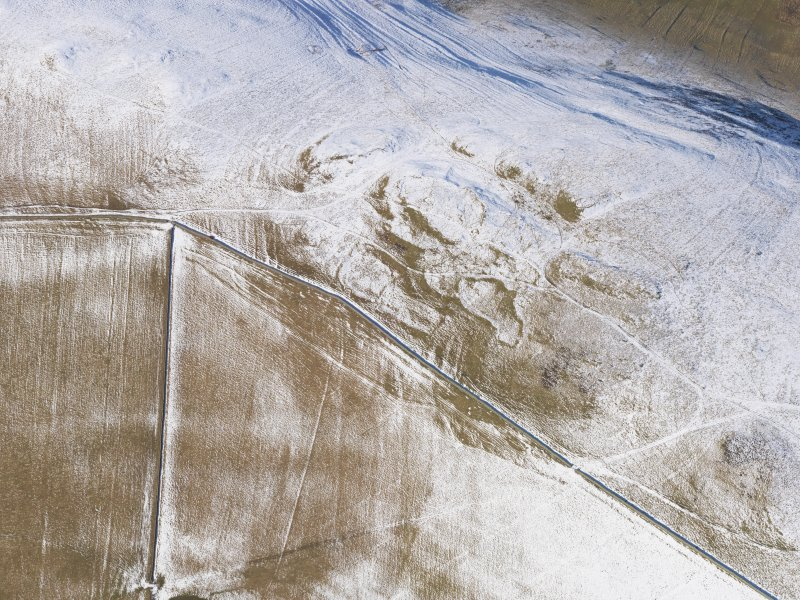Oblique aerial view of fort, enclosures, settlement, rig, cord rig and cultivation terraces under snow, looking WNW.