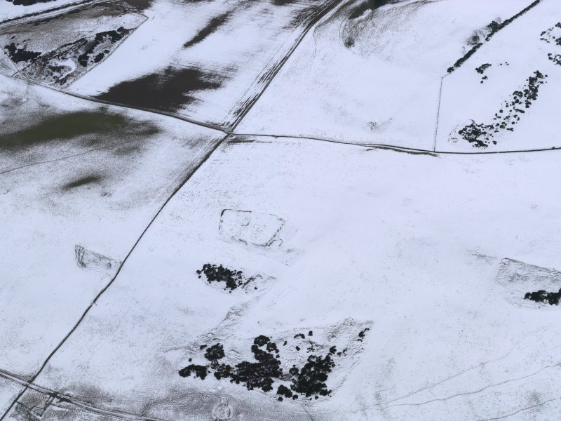 Oblique aerial view of the snow-covered remains of the settlement at Mire Loch, taken from the NNE.