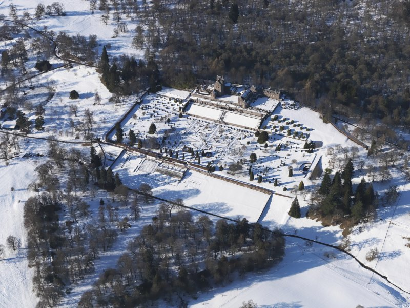 Oblique aerial view of Drummond Castle and gardens under snow, looking NNW.
