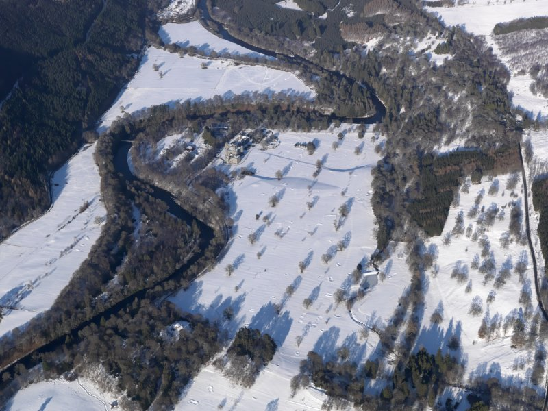 Oblique aerial view of Taymouth Castle and golf course under snow, looking NNE.