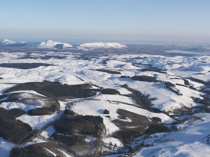 General oblique aerial view towards the snow-covered Lomond Hills, looking SE.