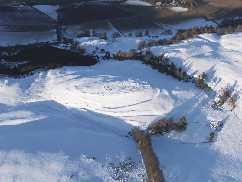 Oblique aerial view of Castle Law fort under snow, looking NE.
