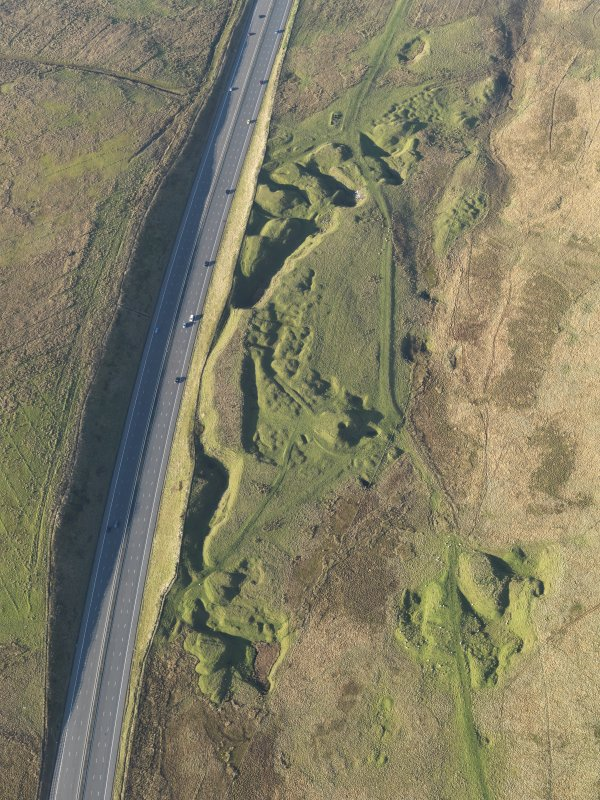 Oblique aerial view of the M74 motorway and the remains of the limestone quarries and lime workings on Wedder Law, taken from the SE.