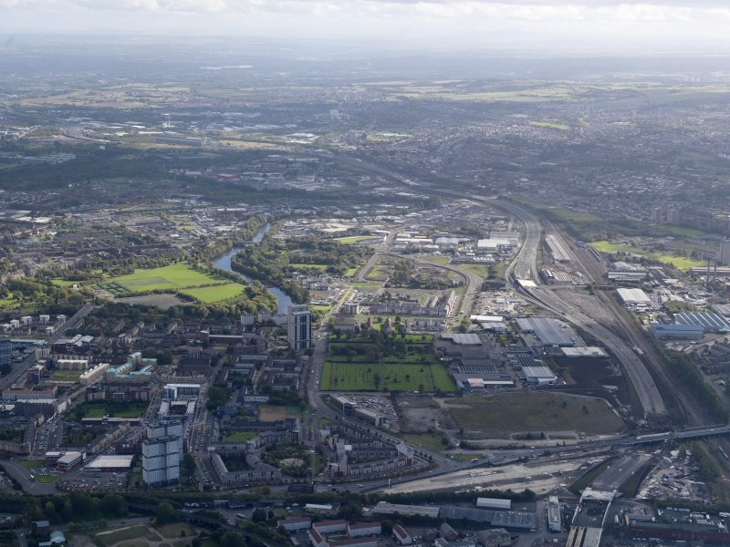 Oblique aerial view of the city showing the route of the M74 extension going from the Port Eglinton area to Polamdie area centred on the Power Motive Works looking E to the Shettleston area, taken from the W.