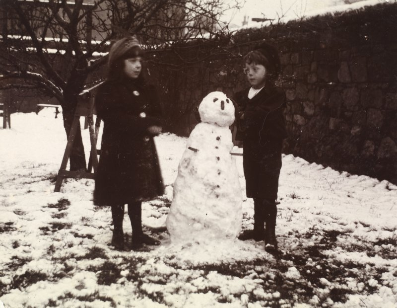 View of two children with a snowman in garden. Page 18/8 PHOTOGRAPH ALBUM NO 34: 16 LEAMINGTON TERRACE, MATHER FAMILY ALBUM