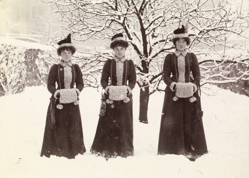 View of three ladies dressed in matching coats and handwarmers in the snow.