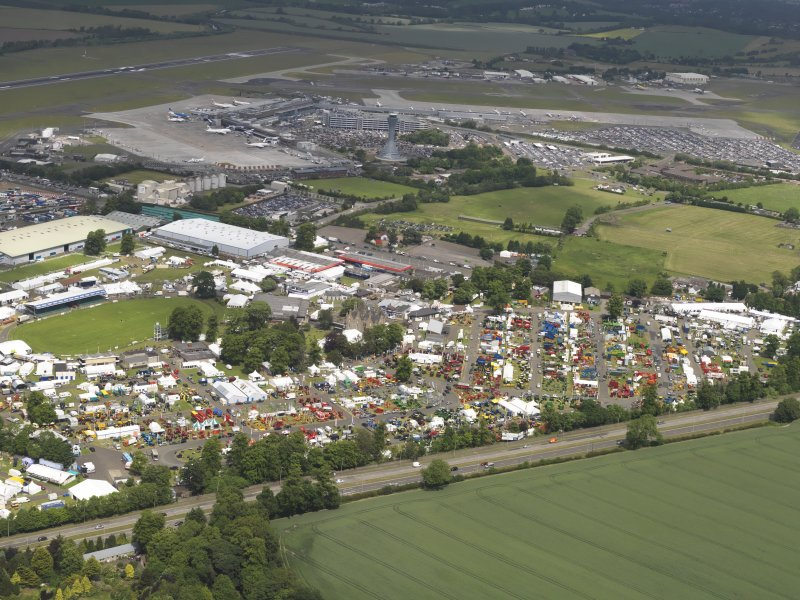 General oblique aerial view of the Royal Highland Showground with Edinburgh airport in the background, taken from the SSW.