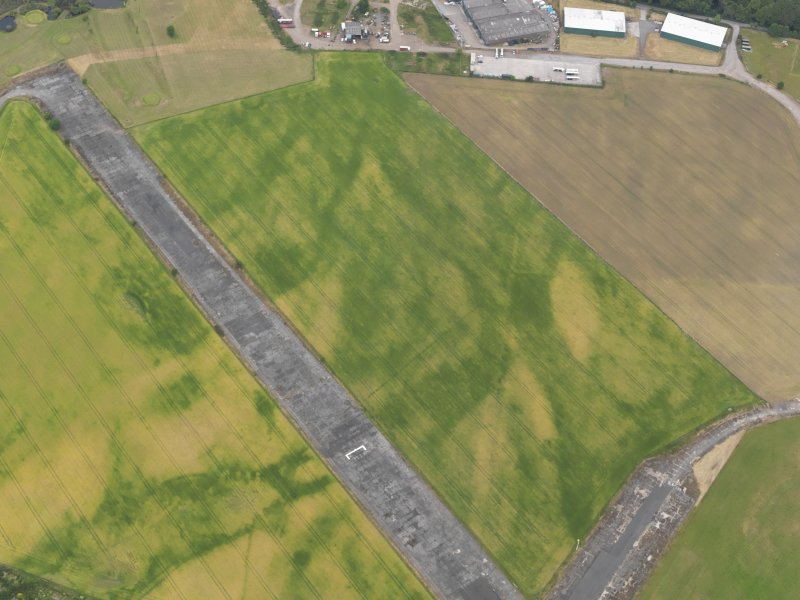Oblique aerial view of the cropmarks of the ring ditch and the field boundaries at Castle Kennedy airfield, taken from the ESE.