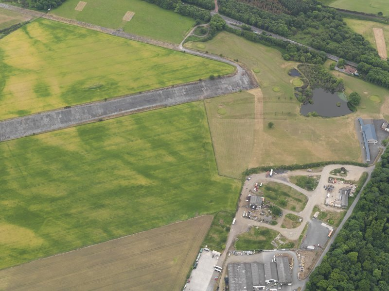 Oblique aerial view of the cropmarks of the ring ditch and the field boundaries at Castle Kennedy airfield, taken from the NNE.