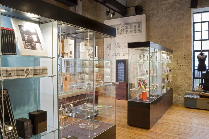 Display cases in School of Art gift shop, with exhibition area beyond.