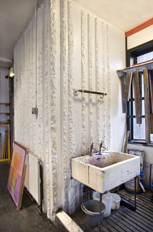 View of exposed corrugated concrete in wet workspace of printmaking studio within Newbery Tower