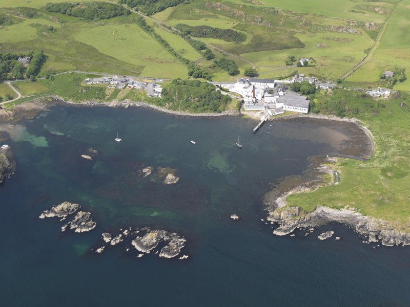 Oblique aerial view of Lagavulin Distillery and the remains of Dunyvaig Castle, taken from the SSE.