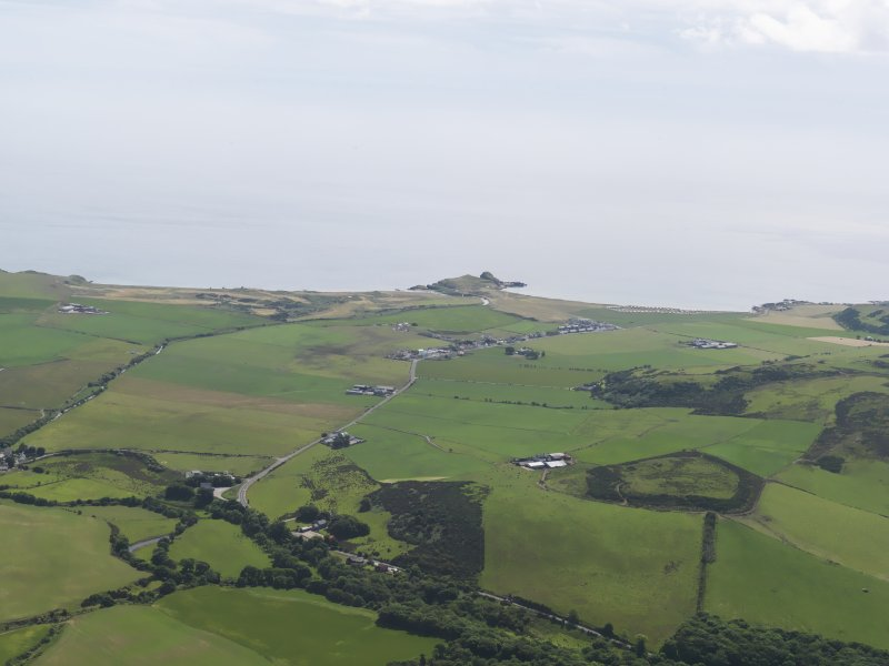 General oblique aerial view looking across the remains of the fort at Cnoc Araich towards the remains of Dunaverty Castle in the distance, taken from the N.