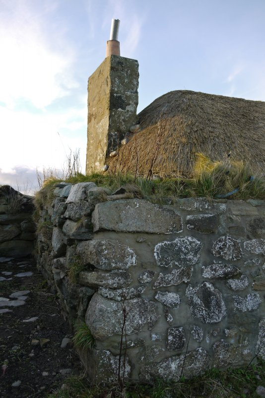 Detailed view of the South-Eastern corner of the thatched cottage at 13 Kilmoluaig, Tiree. The image shows the battered rubble stonework, with grass growing on the tobhta (wallhead), chimney, and that ...