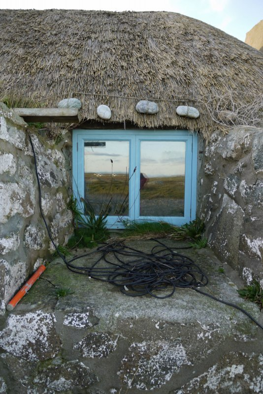 Detailed view of the Northern window to the East elevation of the thatched cottage at 13 Kilmoluaig, Tiree. The image shows the splayed window opening within the thick, battered wall. Stones tied to r ...