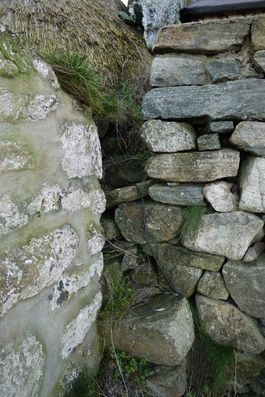 Detailed view of the junction between the East elevation of the thatched cottage at 13 Kilmoluaig, Tiree, and the adjoining building. Makeshift steps can be seen, which give access to the wallhead.