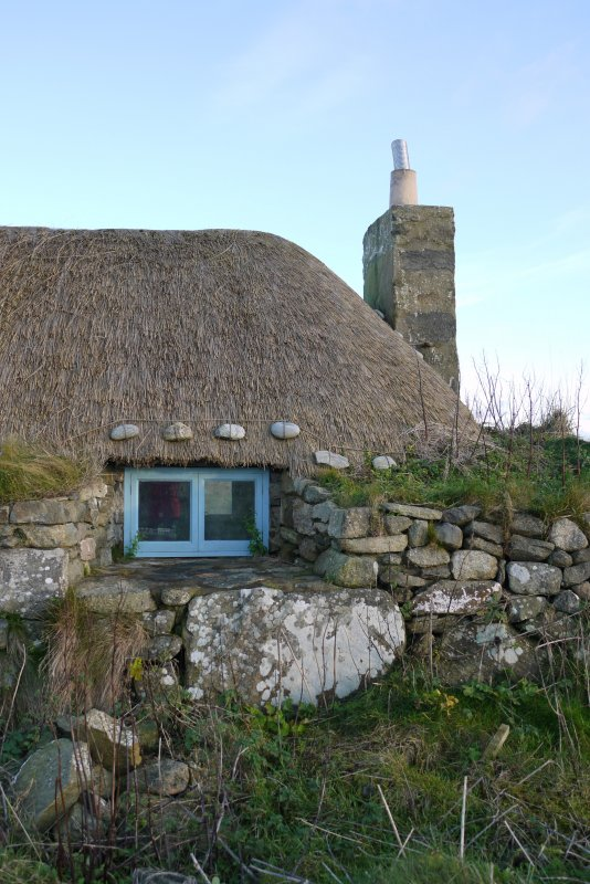 Detailed view of the Southern window to the West elevation of the thatched cottage at 13 Kilmoluaig, Tiree. The image shows the splayed window opening within the thick, battered wall. Stones tied to r ...