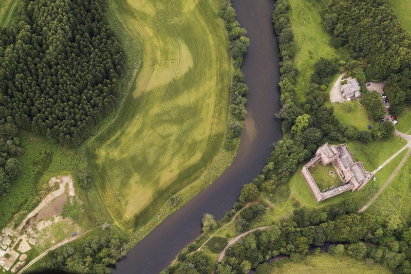 Oblique aerial view of the cropmarks of the pits with the excavation and Doune Castle adjacent, looking to the NW.
