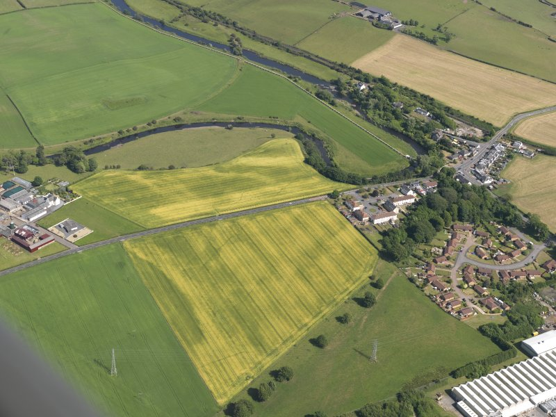 General oblique aerial view of the cropmarks of the cursus monument and pits with Drybridge village adjacent, taken from the W.
