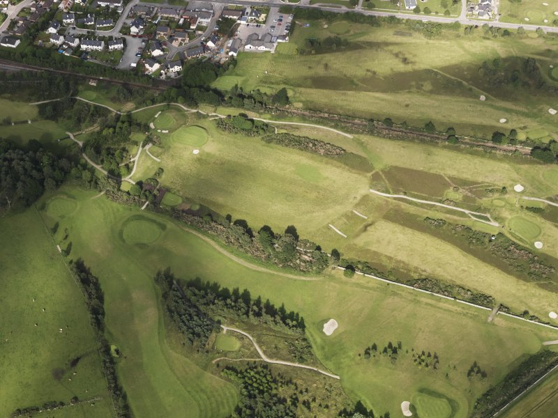 Oblique aerial view of the parchmarks of the barrow on Muir of Ord golf course, looking to the ENE.