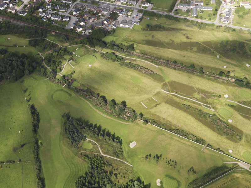 Oblique aerial view of the parchmarks of the barrow on Muir of Ord golf course, looking to the NE.
