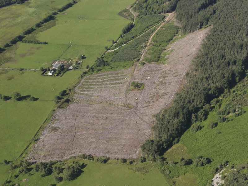 Oblique aerial view of Inchindown oil storage site, showing buildings on the surface, filter beds, square water reservoir and a trackway running from middle to top of photograph which ran between the two tunnel portals and to the spoil heap at the top of the image, taken from the ENE.