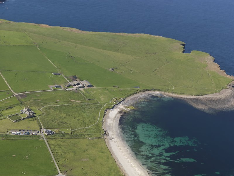General oblique aerial view of the Bay of Skaill centred on Skara Brae, taken from the NE.