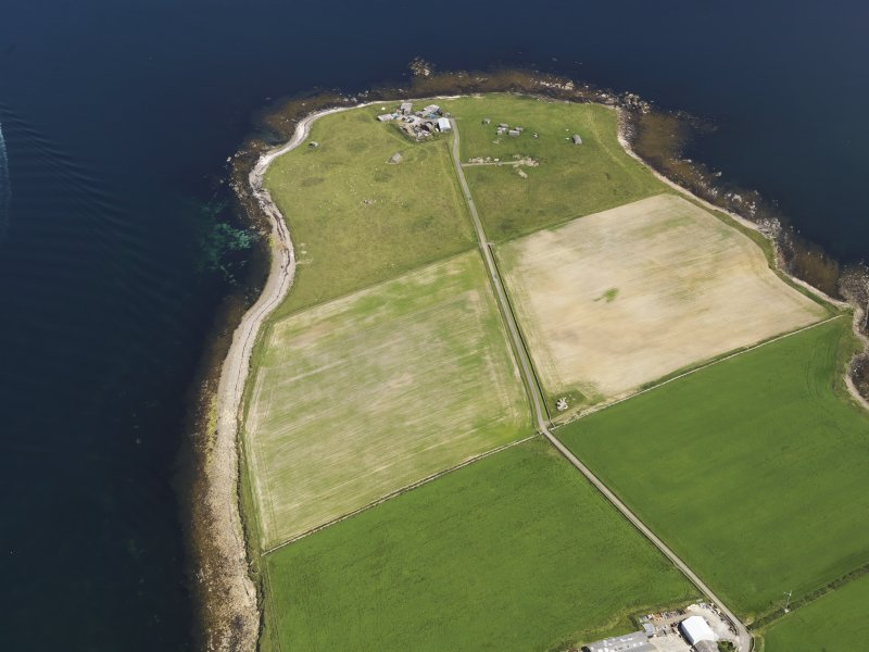 General oblique aerial view of the cropmarks of the barrow cemetery at Carness with the battery beyond, taken from the SW.