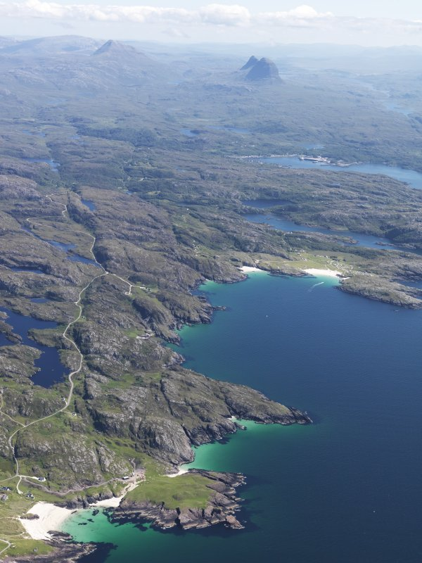 General oblique aerial view looking down the coast with the a' Chlach Thuill dun in the foreground, Lochinver in the middle distance and Canisp and Suilven beyond, taken from the WNW.