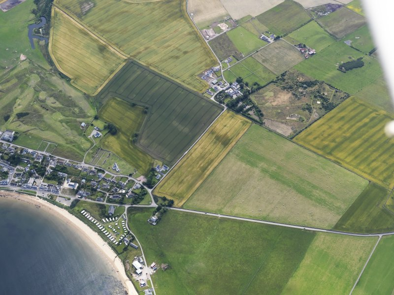 Oblique aerial view of Portmahomack centred on the church, looking SE.