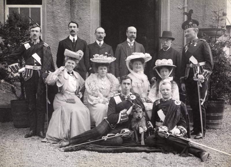 Group of 12 people outside entrance, possibly at Aikenshaw.  Titled: 'S K Turnbull, A Arrol Snr, Montagu Baird, Campbell of Cambusaskin, Franklyn Baird, A Theo Arrol, Miss Wm Arrol, Baroness V Grote,  ...