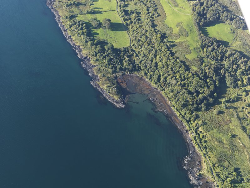 Oblique aerial view of the fort, tower house and fish trap at Caisteal nan Con, looking NE.