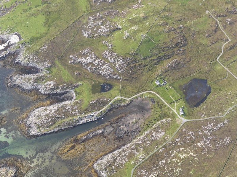 Oblique aerial view of the bay with the pier and Dun Mor a' Chaolais broch adjacent, looking to the WNW.